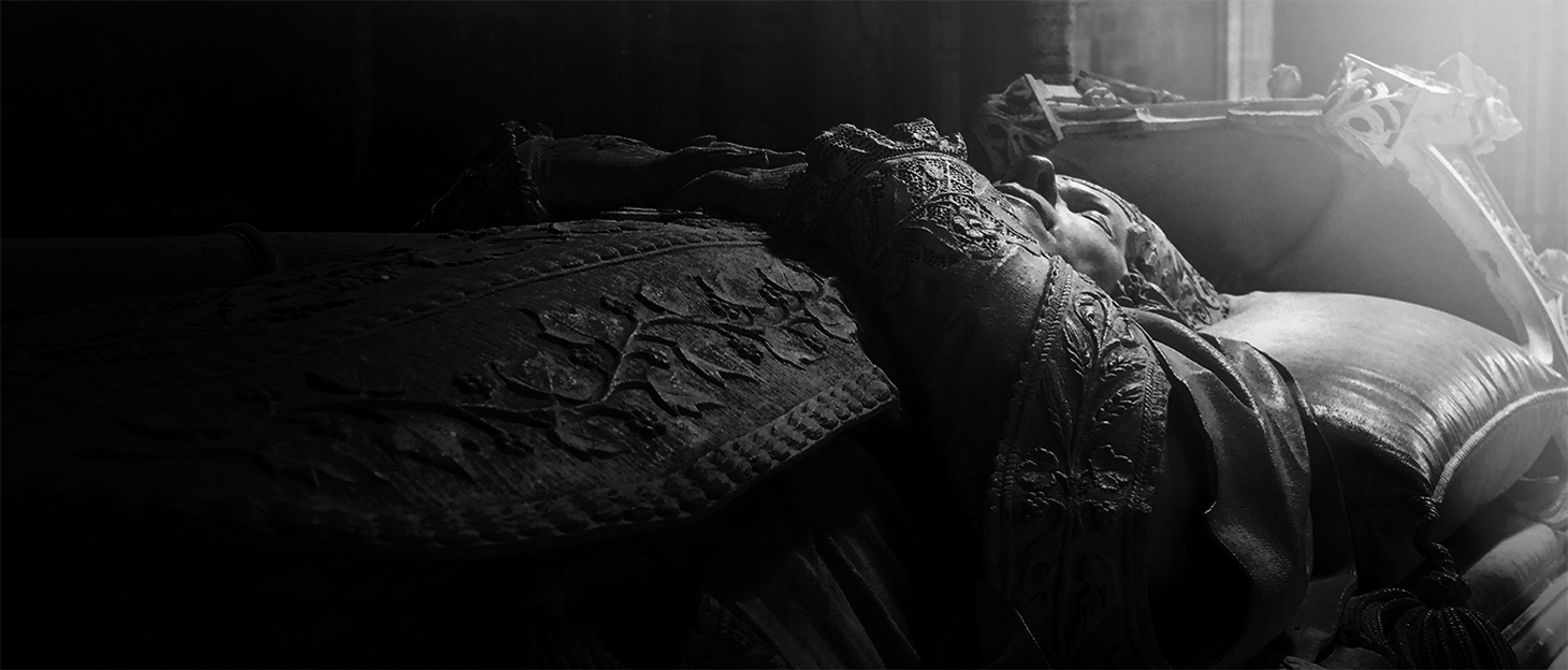 Black and White photography of a sculpture of a dead man laying on a bed in a Cathedral