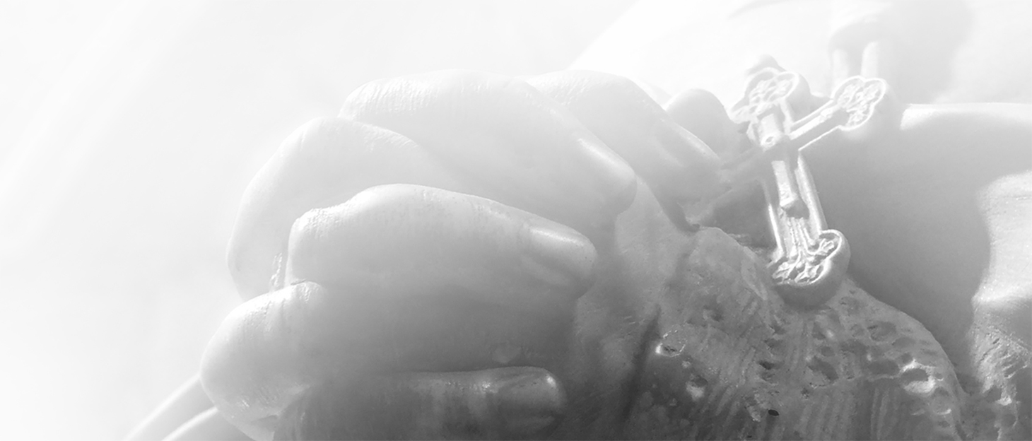 Close up Black and White photography of a Sculpture of priest praying in a cathedral