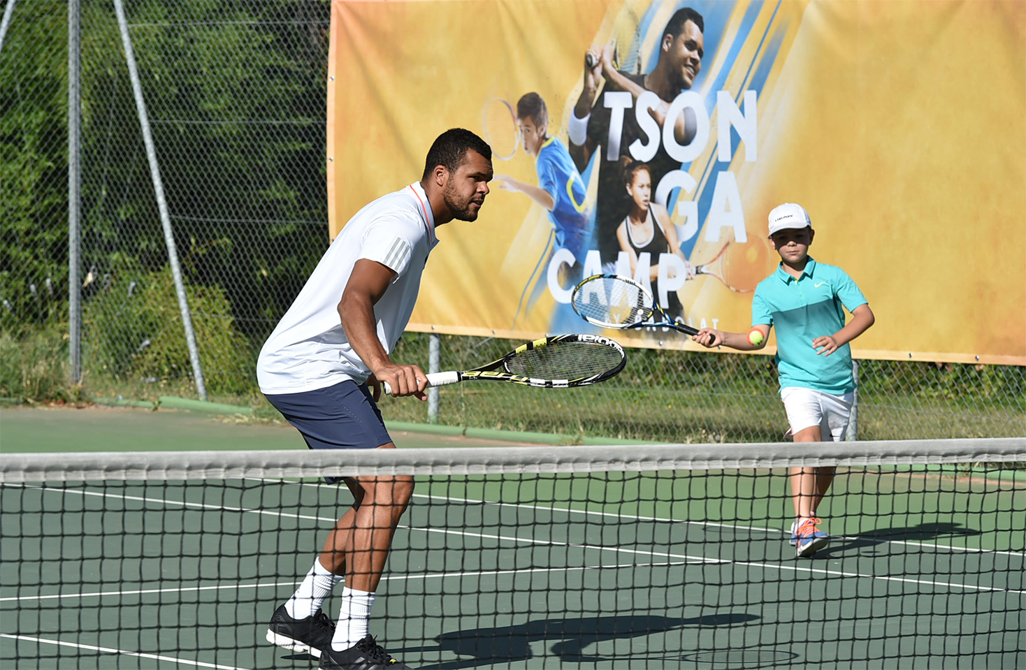 Tsonga playing tennis at his Tsonga camp behind the key visual with a kid in Lyon
